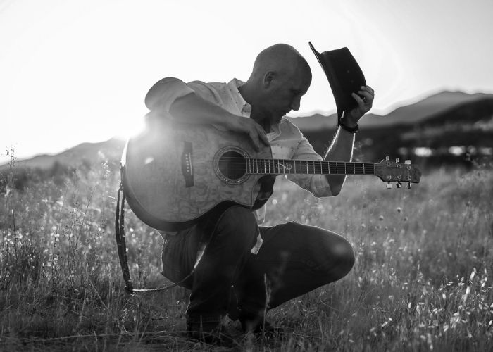 Matthew Morn holding guitar in a field image